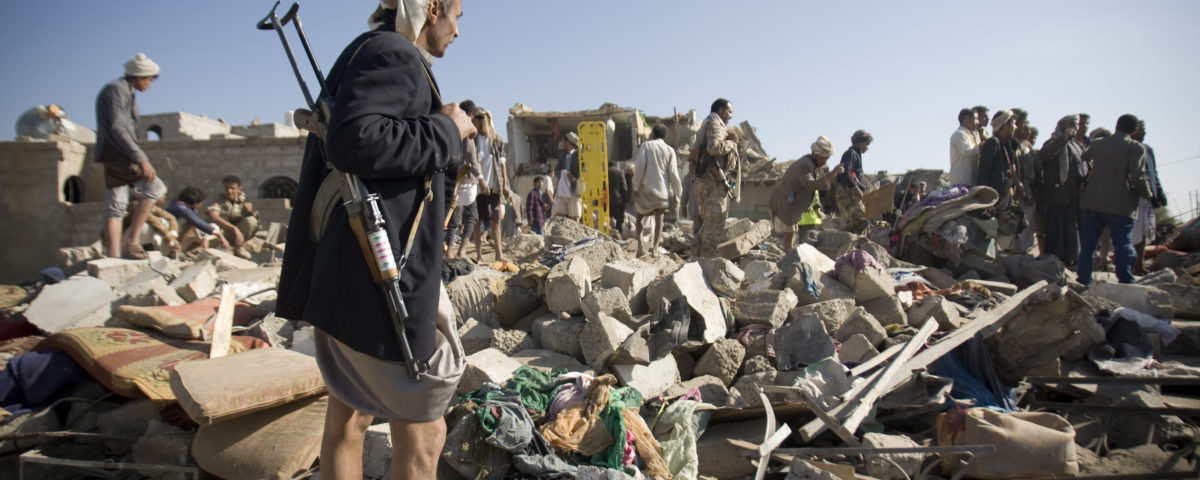 FILE - In this Thursday, March 26, 2015 file photo, a Houthi Shiite fighter stands guard as people search for survivors under the rubble of houses destroyed by Saudi airstrikes near Sanaa Airport, Yemen. Saudi Arabia launched airstrikes Thursday targeting military installations in Yemen held by Shiite rebels who were taking over a key port city in the country's south and had driven the embattled president to flee by sea, security officials said. (AP Photo/Hani Mohammed, File)